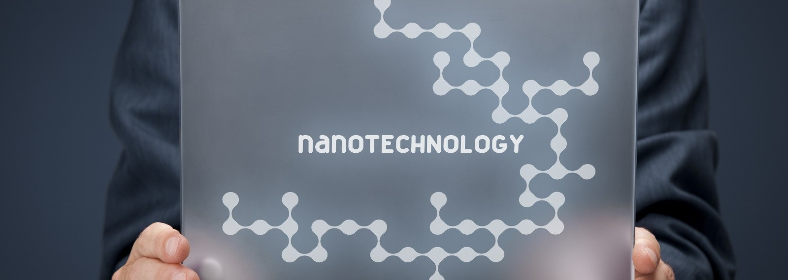 Nanotechnology concept. Man holding futuristic tablet pc with nanotechnology design.